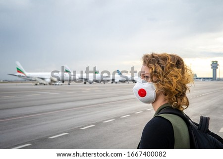 Woman with a mask on her mouth protects against the virus. Sadly looks at the aircraft parked at the airport. Canceled flights due to coronavirus #1667400082