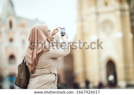 Middle aged Muslim woman wearing hijab standing in urban environment and taking photos by her smartphone.
