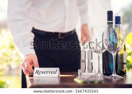 Restaurant waiter placing a reserved table sign with place setting and wine glasses ready for a party Royalty-Free Stock Photo #1667433265