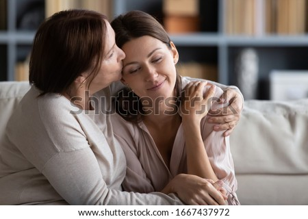 Kind loving senior mature mother feeling happy after calming young daughter, sitting together on couch. Affectionate middle aged mom kissing embracing pleasant peaceful grownup child at home. #1667437972