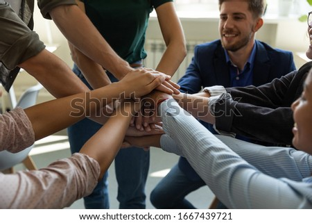 Close up of overjoyed diverse businesspeople stack hands engaged in teambuilding activity at briefing, excited multiracial colleagues motivated for shared business success in training at meeting #1667439721