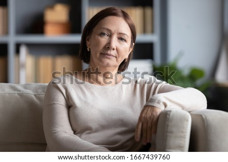 Head shot portrait peaceful tranquil middle aged old woman resting on cozy sofa alone at home. Pleasant happy senior mature 60s grandmother relaxing on couch in living room, posing for photo. #1667439760