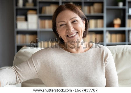 Head shot close up portrait happy healthy middle aged woman sitting on comfortable couch at home. Smiling pleasant 50s elderly mother looking at camera, posing for photo in modern living room. #1667439787