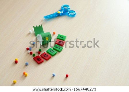 Easter concept greeting card for children or education. The word Easter is composed of individual letters. Near the scissors. Craft bird on the table. Horizontal. Top view  . Daylight. Copy space. #1667440273