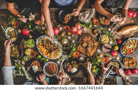Flat-lay of family feasting with Turkish cuisine lamb chops, quince, bean, vegetable salad, babaganush, rice pilav, pumpkin dessert, lemonade over rustic table, top view. Middle East cuisine Royalty-Free Stock Photo #1667441644