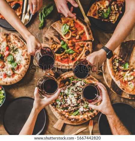 Family or friends having pizza party dinner. Flat-lay of people clinking glasses with red wine over rustic wooden table with various kinds of Italian pizza, top view, square crop. Fast food lunch #1667442820