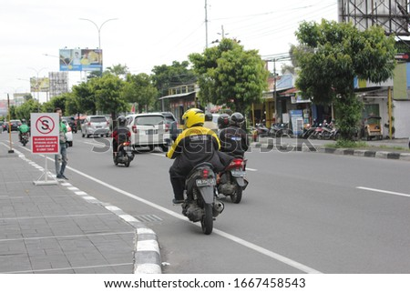 Yogyakarta, Indonesia - March 08, 2020: Maxim's online motorcycle taxi with a yellow jacket will pick up passengers. #1667458543