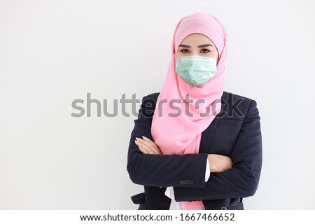 Pretty and confident muslim young asian woman wearing blue suit with medical protective face mask to protect infection from Coronavirus in studio on isolated white background portrait. Covid19 concept #1667466652