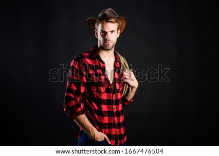 Cowboy wearing hat hold rope. Lasso tool of American cowboy. Still used on ranches to capture cattle or other livestock. Western life. Lassoing on prairie. Man unshaven cowboy black background.