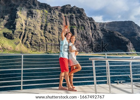 Hawaii cruise ship couple tourists taking selfie with mobile phone at Na Pali coast famous attraction in Kauai island, majestic dramatic landscape.