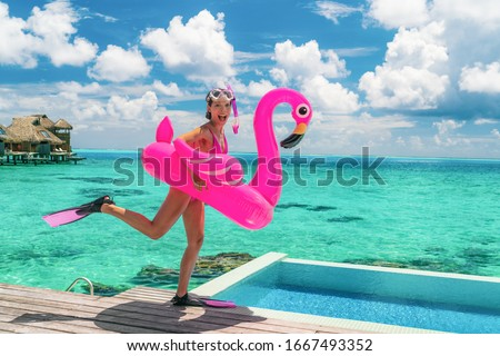 Happy fun beach vacation woman tourist ready to take the plunge jumping in luxury swimming pool at Tahiti resort hotel with snorkel fins and pink flamingo pool float. Funny girl running on holidays. #1667493352