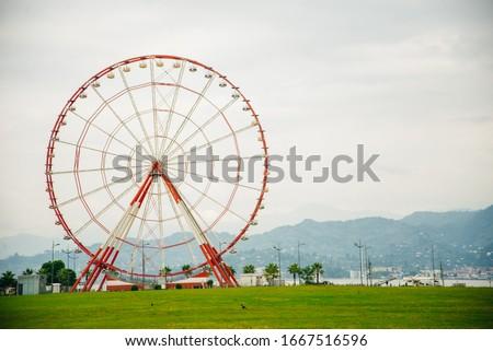 Ferris wheel on embankment of Batumi at sunny day.... Royalty-Free Stock Photo #1667516596