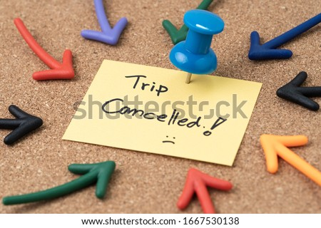 Flight cancelled due to COVID-19 virus spread outbreak, cancel plan to travel reminder concept, Thumbtack pushpin with multi arrows pointing to small paper note written the word Trip Cancelled. #1667530138