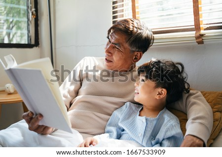 Old man with gray hair tell the bedtime story for his grandson for daytime sleep. Royalty-Free Stock Photo #1667533909