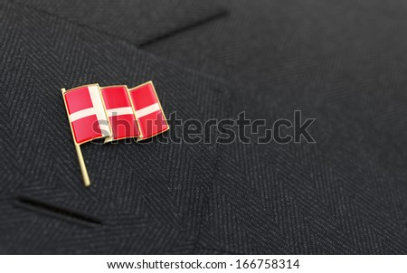 Denmark flag lapel pin on the collar of a business suit jacket shows patriotism #166758314