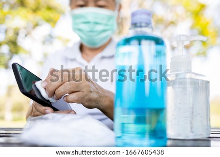 Cleaning mobile phone to eliminate germs,Covid-19hands of senior woman cleaning the phone by hand sanitizer gel,elderly using cotton wool with alcohol to wipe to avoid contaminating with Coronavirus #1667605438