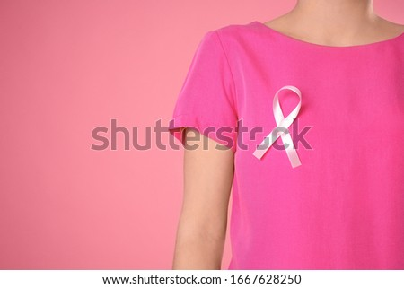 Closeup view of woman with pink ribbon on color background, space for text. Breast cancer awareness #1667628250