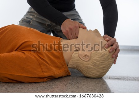 Man teaching cardiopulmonary resuscitation with a dummy on a white background. Front-chin Maneuver and airways opening (Photo 5 of 18). Royalty-Free Stock Photo #1667630428