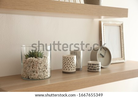 Wooden shelves with plant, clock and photo frame on light wall #1667655349