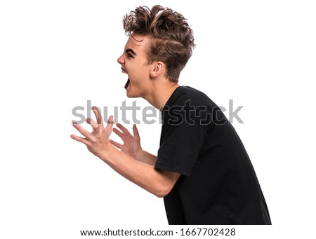 Profile of Rebellious teen boy dressed in black, isolated on white background. Angry screaming teenager in style of punk goth wearing black t-shirt, shouting. Problems of transitional age. Side view