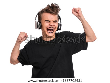 Rebellious happy teen boy with headphones, isolated on white background. Cheerful child listening to music and singing song. Emotional portrait of teenager in style of punk goth enjoying music.