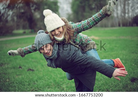 Colourful pic with beautiful young couple who  have fun together , autumn background ,atmospheric place, green grass background