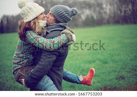 Colourful pic with beautiful young couple kissing each other and have fun together , autumn background ,atmospheric place