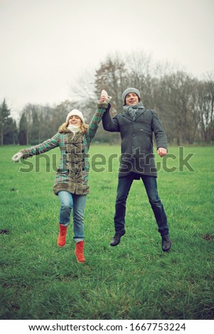 Colourful pic with beautiful young couple who  have fun together , autumn background ,atmospheric place, jumping people