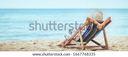 Summer travel beach vacation concept, Traveler asian woman with hat and dress relax on chair beach at Pattaya, Chon Buri, Thailand #1667768335