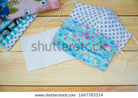 Top view of Stack cotton, white tissue paper and DIY fabric cotton face mask on wood table. Protect saliva, cough, dust, pollution (PM2.5), Virus, Bacteria, COVID-19. Handmade concept. Copy space. Royalty-Free Stock Photo #1667783314