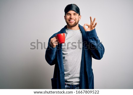 Young blond man with beard and blue eyes wearing pajama drinking cup of coffee doing ok sign with fingers, excellent symbol #1667809522