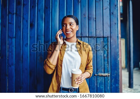 Cheerful female with caffeine beverage in hand enjoying friendly smartphone communication during leisure at loft urbanity, happy hipster girl making sincerely conversation via cellphone application Royalty-Free Stock Photo #1667810080