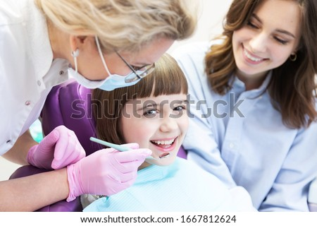 Mother with  daughter at dentist appointment in clinic for kid. Girl looking at camera. Professional stomatologist examining child teeth with mouth mirror. Pediatric dentistry #1667812624