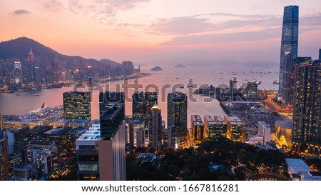 Aerial scenery panoramic view of Hong Kong Evening with metropolitan bay Victoria Harbor at sunset. Lighted Modern cityscape, urban skyline buildings. Energy power infrastructure. Popular Asian city