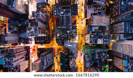 Aerial top view of downtown district  buildings in night city light. Bird's eye view from drone of cityscape metropolis infrastructure, crossing streets with parked cars. Development infrastructure Royalty-Free Stock Photo #1667816290