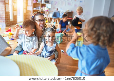 Beautiful teacher and group of toddlers playing around lots of toys at kindergarten Royalty-Free Stock Photo #1667835010