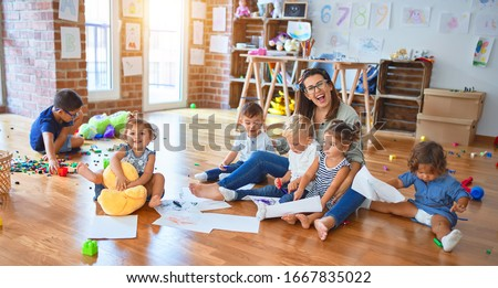 Beautiful teacher and group of toddlers sitting on the floor drawing using paper and pencil around lots of toys at kindergarten Royalty-Free Stock Photo #1667835022