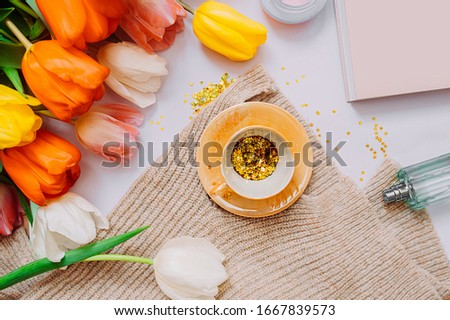 spring mood Board of tea party. A bouquet of bright tulips of different colors, small Golden Cup filled with gold spangles stars , perfume, book, light white background. Flat lay, top view #1667839573
