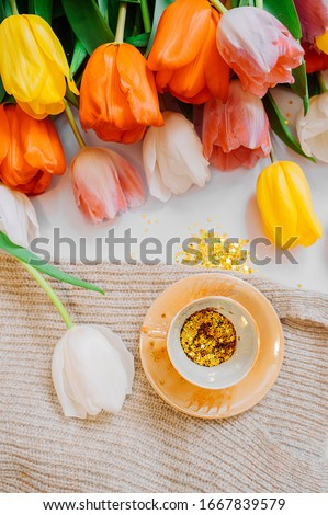 spring tea party. small gold cup filled with gold spangles stars and saucer on a light background with a bouquet of multi-colored tulips. Flat lay, top view, Vertically #1667839579