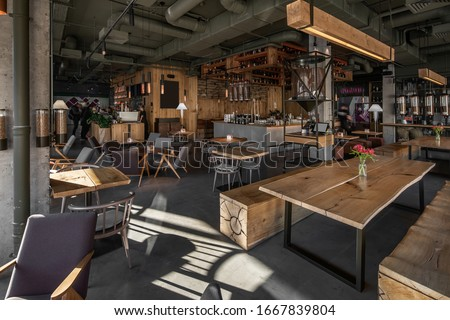 Restaurant in a loft style with textured wooden walls and concrete columns. There are tables with chairs, many shelves with bottles, glass coffee bean dispensers, coffee machines and equipment. #1667839804