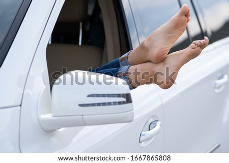 Close up of woman driver bare feet sticking out of a car open window. #1667865808