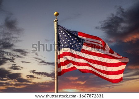 An American flag on flagpole waving in the wind under clear blue skies Royalty-Free Stock Photo #1667872831