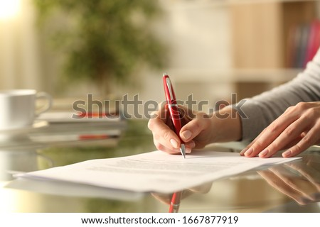 Close up of woman hands signing document with pen on a desk at home Royalty-Free Stock Photo #1667877919