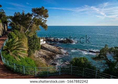 "Genoa, Italy. Horizontal view of the promenade of Nervi ""Anita Garibaldi"" on a sunny day. Walk characterized by trees, sea, rocks and red pavement Royalty-Free Stock Photo #1667882242"