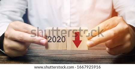 Businessman holds wooden blocks 2020 with down arrow. Economic crisis and recession. Bankruptcy and finance crisis. Analysis and analytics. Results of the year Royalty-Free Stock Photo #1667925916