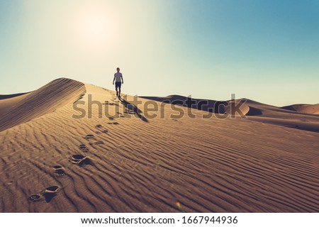 Man in summer clothes with sunglasses is going down the red dune tracing his footprints during sunny day in UAE Liwa desert, at the beautiful rippled sand  #1667944936