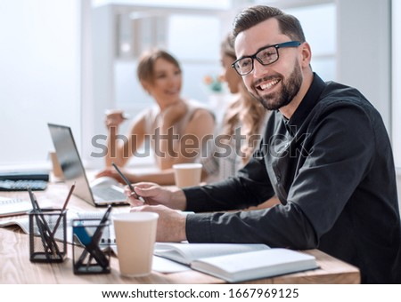 smiling businessman in the workplace in the office #1667969125