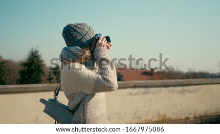 Medium Shot of Young Tourist Woman Walking near Medieval Castle and Taking Pictures by Vintage Camera with Beautiful Sun Glare