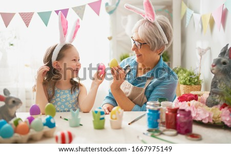 Happy easter! A grandmother and her granddaughter painting Easter eggs. Happy family preparing for Easter. Cute little child girl wearing bunny ears on Easter day.                                #1667975149