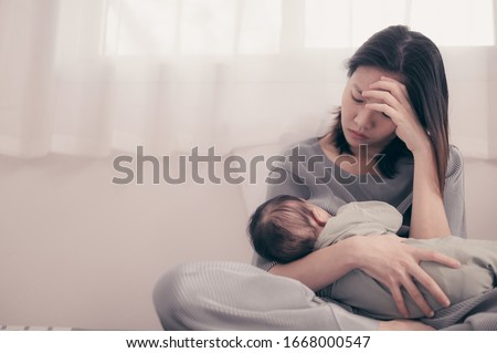 Tired Mother Suffering from experiencing postnatal depression.Health care single mom motherhood stressful. Royalty-Free Stock Photo #1668000547
